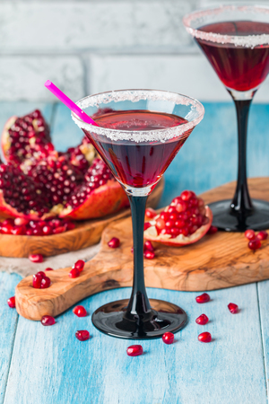 coctel de frutas: pomegranate cocktail  and ripe red pomegranate fruit on blue wooden table
