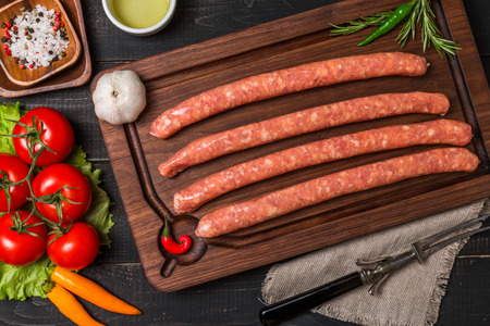 sausage: Raw sausage with spices and  vegetables on a dark wooden background, top view