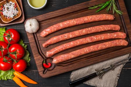 saucisse: saucisse crue avec des �pices et des l�gumes sur un fond en bois sombre, vue de dessus