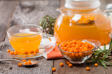 glass cup: Tea with sea buckthorn and honey on wooden background Stock Photo