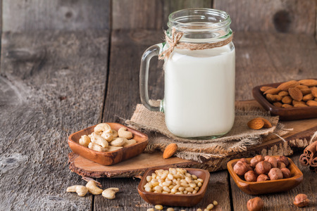 Vegan milk from nuts in glass jar with various nuts on wooden background 스톡 콘텐츠