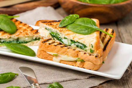 fresh spinach: sandwich with cheese and spinach on wooden background Stock Photo