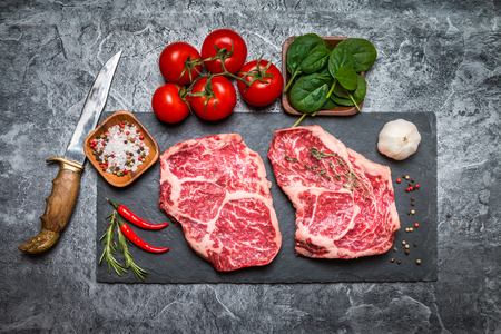 Raw fresh marbled meat Steak with seasonings, herbs and vegatables on grey concrete background, top view