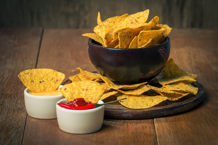 Mexican nacho chips and cheese and salsa dip in bowl on wooden background