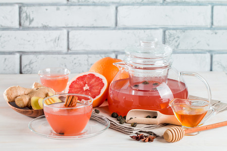Grapefruit herbal tea with ginger and honey in a glass teapot and cup on white wooden background 스톡 콘텐츠