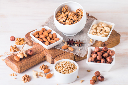 Variety of nuts: almonds, walnuts, hazelnuts cashews and pine nuts in wooden bowls on white wooden background Reklamní fotografie