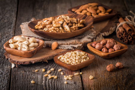 Variety of nuts: almonds, walnuts, hazelnuts cashews and pine nuts in wooden bowls on wooden background