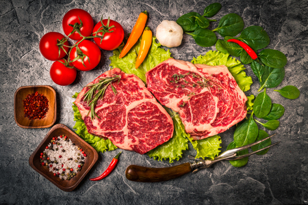 seasonings: Raw fresh marbled meat Steak with  seasonings, herbs and vegatables on grey  concrete background, top view Stock Photo