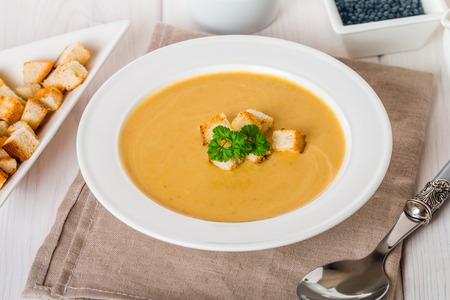 lenteja: Vegetariana de lentejas crema de sopa con trocitos de pan, lentejas y verduras en el fondo de madera blanca