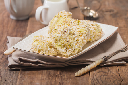 roulade: Meringue roulade with pistachio nut in a white plate on wooden background