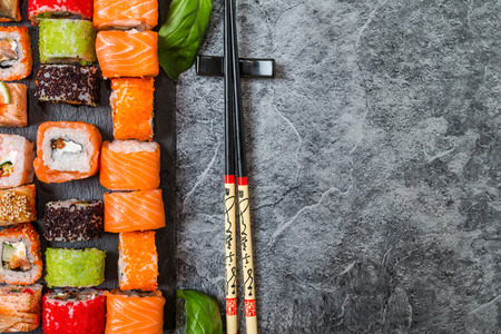 Traditional Japanese food - sushi, rolls and sauce on grey metal background. Top view