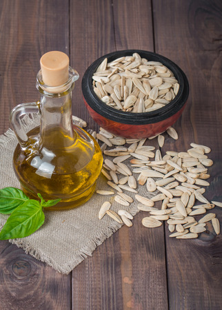 olive green: Sunflower oil and white sunflower seeds on wooden background
