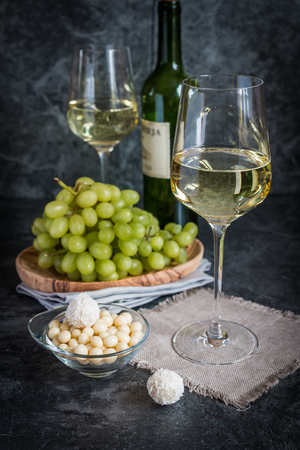 wine and grapes: Bottle of white wine, two glasses and bunch of grapes on gray background Stock Photo