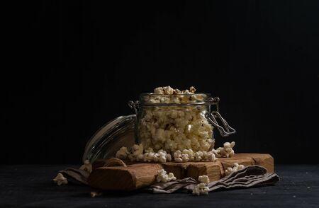 black backgound: Salt popcorn in a glass jar on black backgound Stock Photo