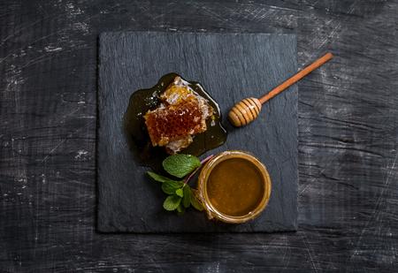 Honey, honeycomb, mint and honey dipper on black slate tray over grunge dark backdrop, top view Reklamní fotografie