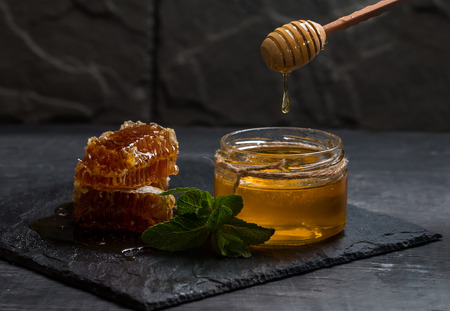 liquid state: Honey dripping from a wooden honey dipper into the glass jar on dark background