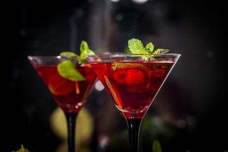copa martini: Dos copas de martini del cóctel de alcohol de color rojo frambuesa con la menta Foto de archivo
