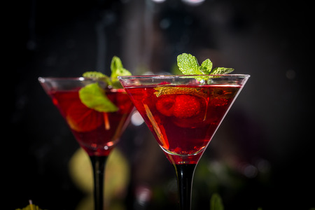 martini glass: Two martini glasses of red alcohol raspberry cocktail with mint