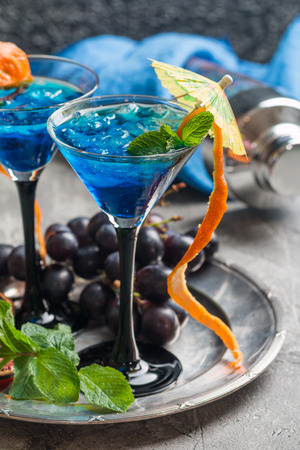 blue hawaiian drink: Blue cocktail with ice and mint in martini glasses on gray background