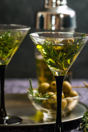 ajenjo: Two fresh green cocktails with rosemary and olives in martini glasses on gray background Foto de archivo