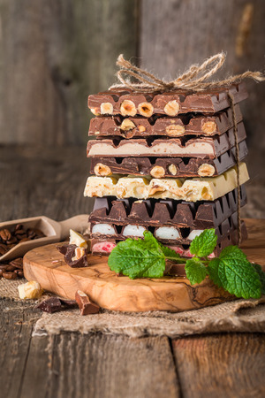 fillings: An assortment of white, dark, and milk chocolate with nuts and with various fillings on wooden background