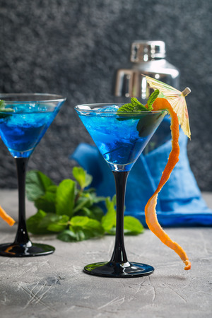 daiquiri alcohol: Blue cocktail with ice and mint in martini glasses on gray background
