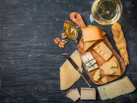 black board: Various types of cheese  on cutting board with white wine on black background, top view