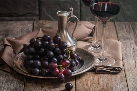 Refined still life of red wine and grapes on metal tray on wooden table, dark background