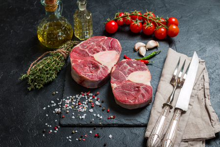 shank: Raw veal shank slices meat and ingredients for Osso Buco cooking on black background, top view