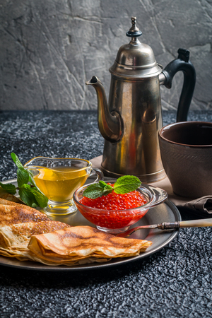 pancake week: Yeast pancakes, traditional for Russian pancake week witn red cavier and honey on metal plate, black background Stock Photo