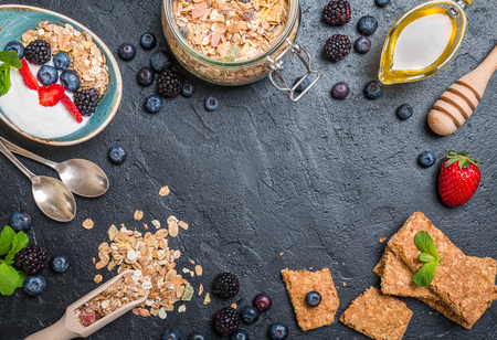 Top view blackboard with copyspace from granola bars and healthy homemade granola with toasted oats, yogurt, honey and berries. Health and diet concept.
