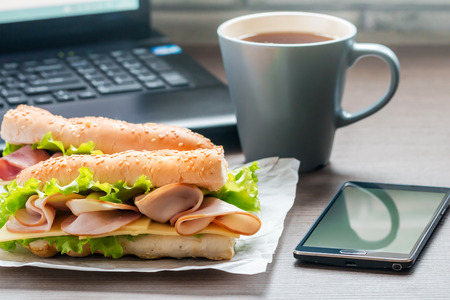 Quick lunch in the office sandwich and a cup of tea on the desktop