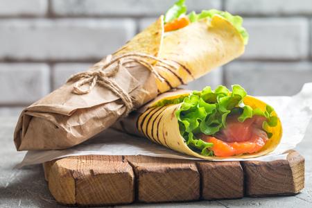Abrigo de la tortilla fresca con verduras y salmón en papel Foto de archivo - 55084221