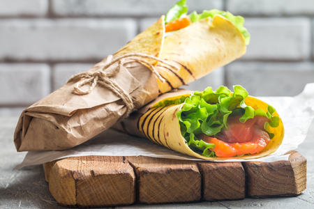 fresh tortilla wrap with vegetables and salmon on paper