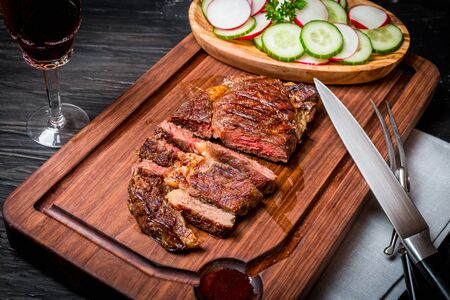redish: Close up sliced medium rare grilled Beef steak Ribeye with cucumber and radish on cutting board on black background, top view