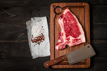 dark meat: Raw fresh meat Club Steak, seasoning and meat chopper  on dark wooden background, top view Stock Photo