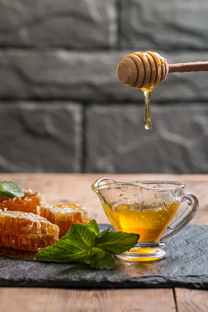 liquid state: Honey dripping from a wooden honey dipper in sauceboat on dark background