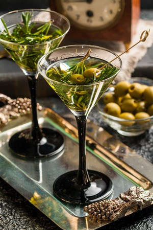martini shaker: Two fresh green cocktails with rosemary and olives in martini glasses on gray background Stock Photo