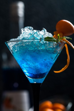 blue hawaiian drink: Blue cocktail in martini glasses with ice and Kumquat on black background Stock Photo