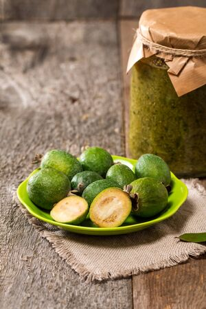 feijoa: Fresh fruits of feijoa in abowl and feijoa jam on wooden table Stock Photo