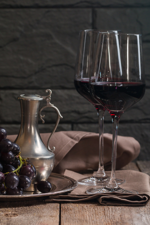 restaurant tables: Refined still life of red wine and grapes on metal tray on wooden table, dark background