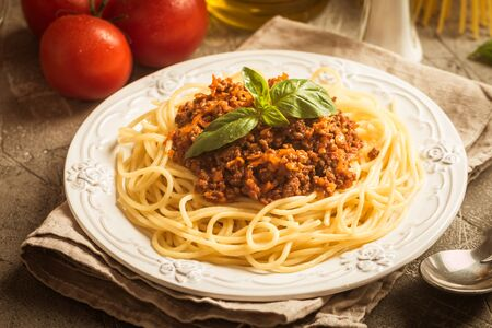 mincemeat: Spaghetti bologneseon white plate with ingredients on gray background