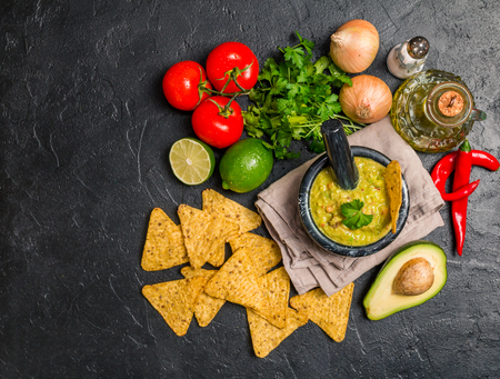 vegetarian food: Bowl of delicious homemade Guacamole with nachos next to fresh ingredients on black background, top view
