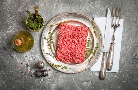 Minced meat on metal plate with seasoning and fresh thyme on gray background, top view