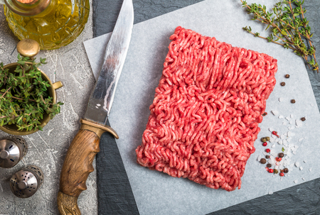 farce: Minced meat on paper and slate with seasoning and fresh thyme on gray background, top view