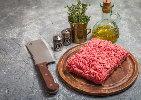 farce: Minced meat on  cutting board with seasoning and fresh thyme on gray background, top view