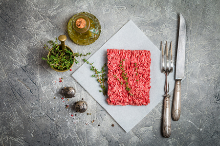 farce: Minced meat on paper with seasoning and fresh thyme on gray background, top view Stock Photo