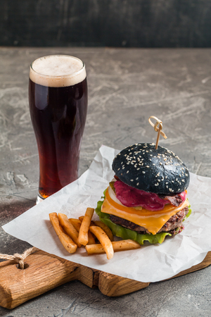 vegetable carbon: Gourmet black burger with berry sauce, french fries and beer on wooden table and dark background Stock Photo