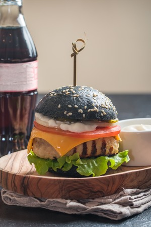 colorant: Homemade black burger with grilled chicken patty on dark background Stock Photo