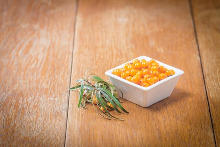 seabuckthorn: Sea-buckthorn berries in white bowl on a wooden background Stock Photo